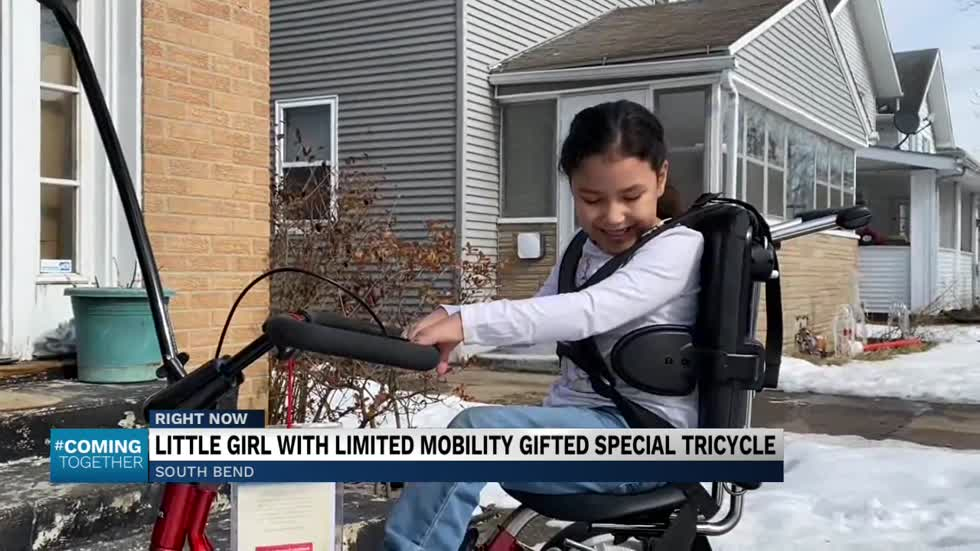 Little girl with limited mobility gifted special tricycle