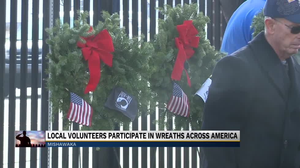 Volunteers place wreaths on the graves of veterans in Mishawaka