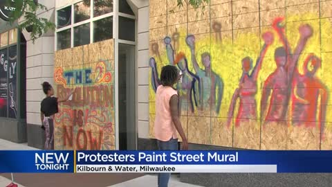 ' Protesters paint large street mural outside Milwaukee City...